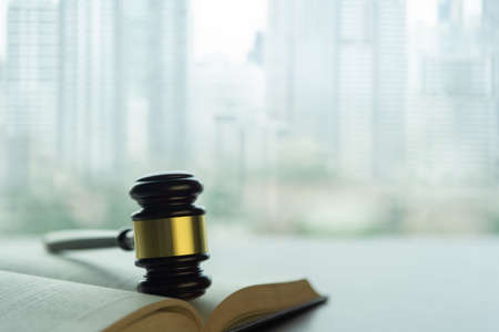 real estate law concept. judge gavel on legal books with city building.