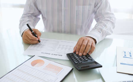 accounting and financial Concept. Business people using a calculator to review financial and business report for evaluate company performance.