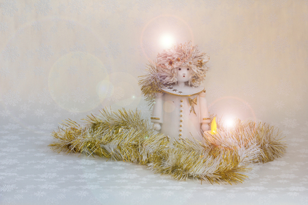 The Christmas Angel sits in the garland surrounded by light. Banco de Imagens