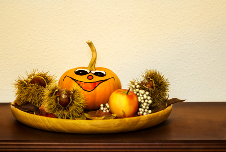 A funny pumpkin sits amidst fruits and nuts. Stock Photo