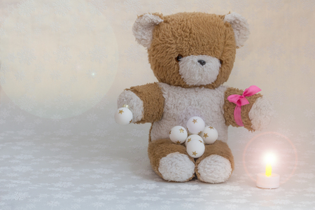 A teddy with pink bow and Christmas balls is waiting for the feast.