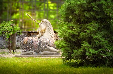 Between the bush and flowers, the unicorn sits in the Micheal-end spa garden in Garmisch-Partenkirchen. Stok Fotoğraf