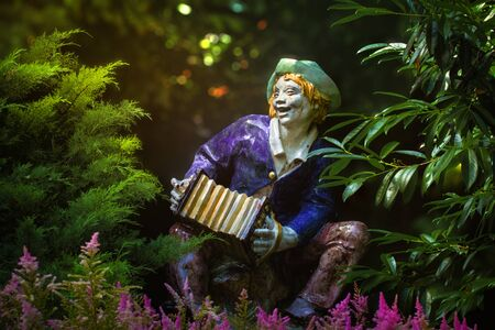 The singing accordion player provides entertainment in the park in the form of a sculpture.