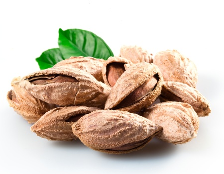 Almond; group of nuts in kernel with leaves. Isolated on a white background. photo