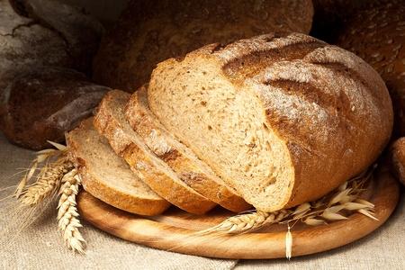 буханка: свежеиспеченный хлеб на деревянной тарелке