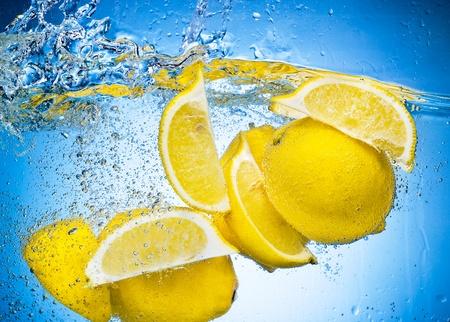 레몬: 레몬 조각 파란색 배경에 큰 스플래시 물에서 깊이 떨어지는 스톡 사진