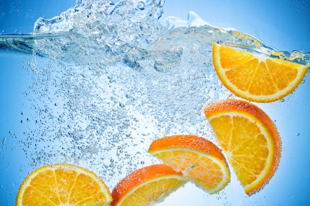 oranges: Orange Slices falling deeply under water with a big splash on blue background Stock Photo