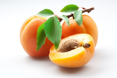 Apricots with leaves on white background, isolated