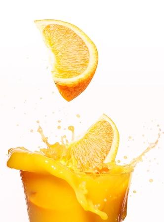 succo di frutta: Fette di arancia cadere in succo. Vetro isolato su bianco Archivio Fotografico