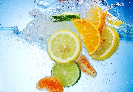 lime slice: Tropical fruits are falling deeply under water with a big splash Stock Photo