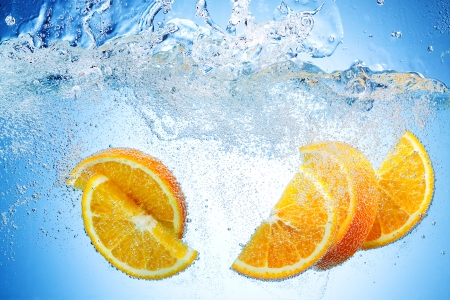 deeply: Orange Slices falling deeply under water with a big splash Stock Photo