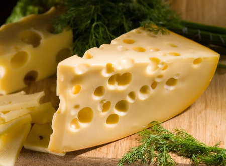making a save: piece of cheese with dill on wooden table Stock Photo
