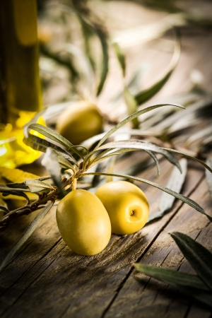Organic olives with bottle of oil on a wooden table photo
