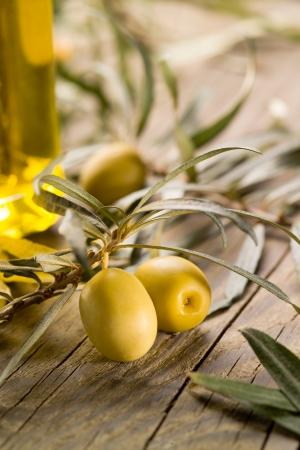 olivo arbol: Aceitunas negras con la botella de aceite en una mesa de madera