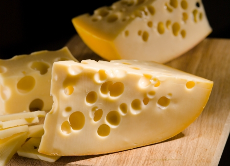 cheez: Cheese with big holes on wooden board Stock Photo