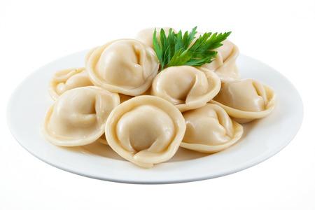 ravioli: Dumplings and parsley - russian pelmeni - italian ravioli - on white plate isolated