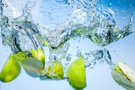 deeply: Green apples. Fruits fall deeply under water with a big splash Stock Photo