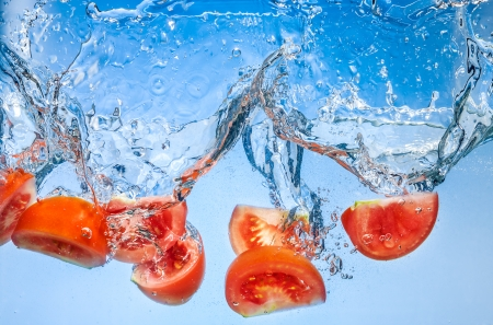 deeply: Tomato. Vegetables fall deeply under water with a big splash Stock Photo