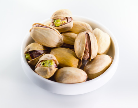 pistachios: Pistachios  Heap of nuts isolated on white background Stock Photo