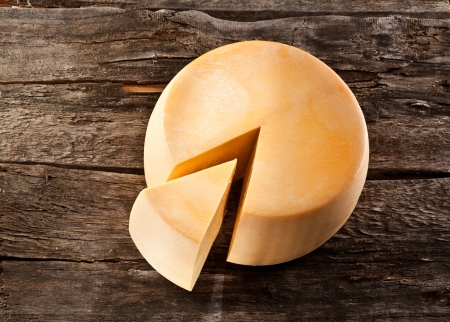 Cheese wheel on wooden table Stock Photo
