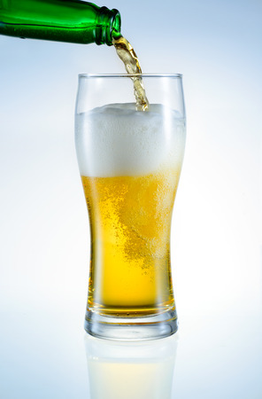 Beer is pouring from bottle  into the glass photo