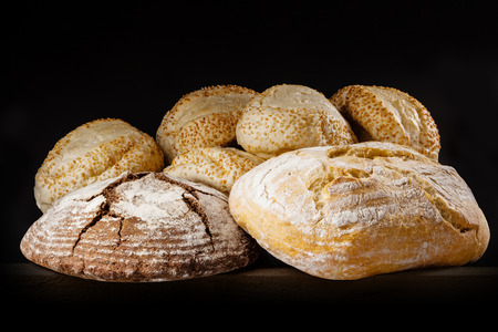 Fresh bread and buns with sesame on dark background. photo