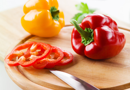 Organic paprika peppers with slice over wooden table