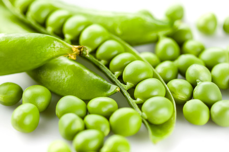 Pods of green peas on white background photo