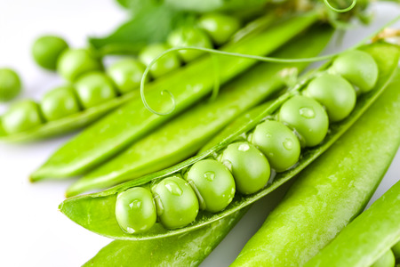 Pods of green peas with drops on white background photo