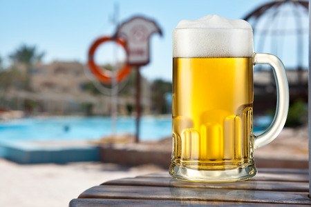 foam party: Mug of light beer on a beach Stock Photo
