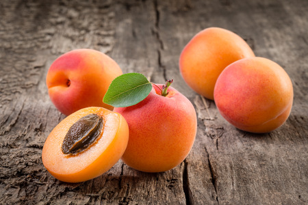apricot kernel: Apricot. Organic fruits with leaf on wooden background Stock Photo