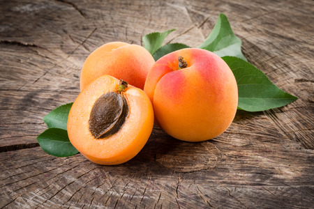 apricot kernel: Organic apricots with leaves on wooden background Stock Photo