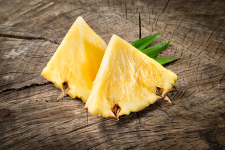 Pineapple. Fruit slices on wood background Reklamní fotografie