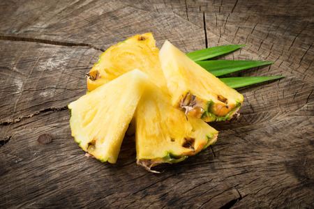 Pineapple slices on wood background