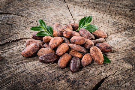 Cocoa beans on wooden background