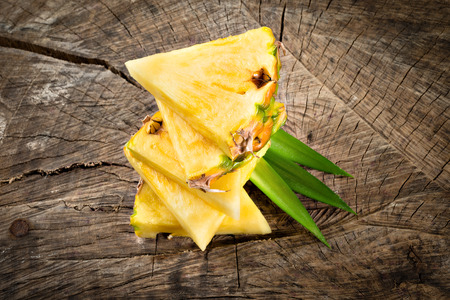 slice: Pineapple slices on wooden background Stock Photo