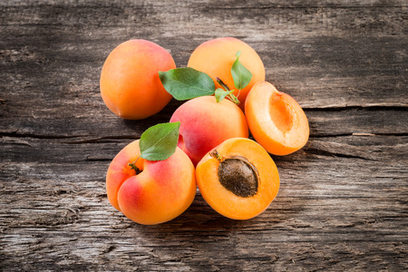 apricot kernel: Apricot with leaves on wooden background Stock Photo
