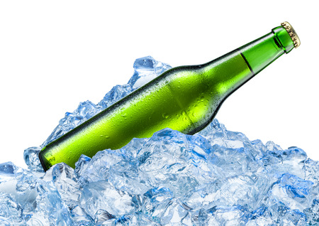 Bottle of beer with drops in ice cubes. Isolated on white. Foto de archivo