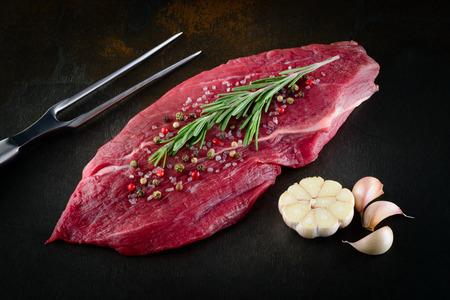 carne cruda: Fresca carne cruda sobre un fondo oscuro. Alimentos orgánicos.