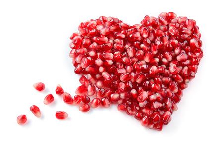 Pomegranate. Fresh raw seeds isolated on white background. Heart shape.