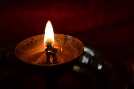 Candle lit in a dark room called diya