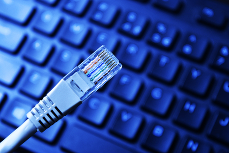 Network cables on black computer keyboard. internet concept. Stock Photo