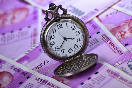 investment concept , Vintage pocket watch on indian 2000 rupees banknotes