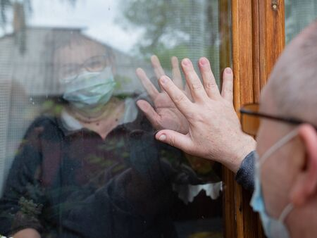 Social distance between older people as a result of the coronavirus pandemic. Communication through the window. Stock Photo