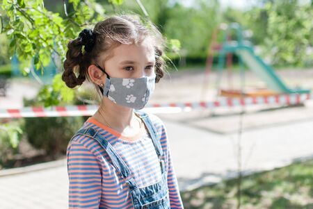 portrait of a little girl in a protective mask on the background of a playground, fenced with a prohibition tape