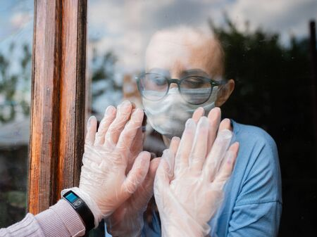 A sad mother holds her hands on the window in front of her childrens hands. Self-isolation in the face of the pandemic