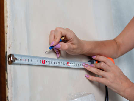 Measuring the walls in the room before pasting Wallpaper, close-up.