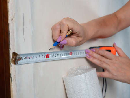 Close-up of a woman measuring the wall with a tape measure in a room for wallpapering.