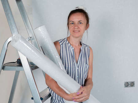 A happy woman holds rolls of new Wallpaper in her hands. Repairs in the apartment. Wallpapering.