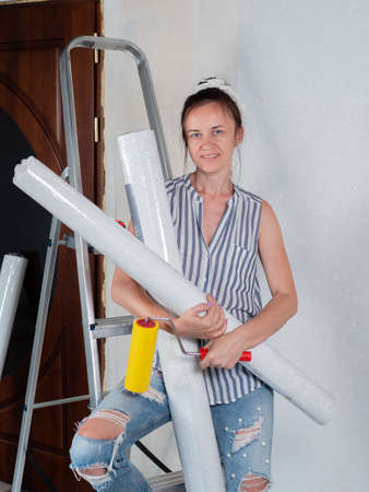 Repairs in the apartment. Wallpapering. Portrait of a woman with rolls of Wallpaper near the stepladder in the room. 免版税图像